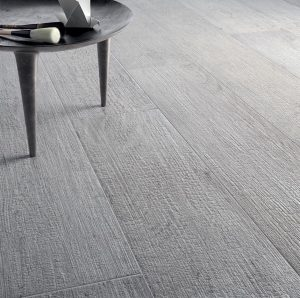 Medium gray wood look porcelain kitchen floor tiles with side table